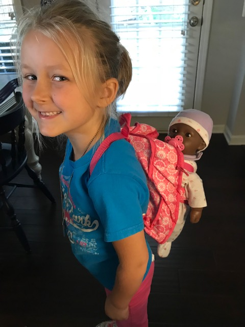 Baby doll in backpack